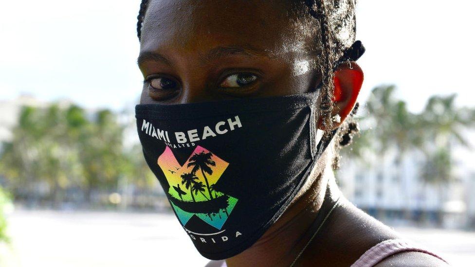 Mujer con mascarilla en Miami Beach.