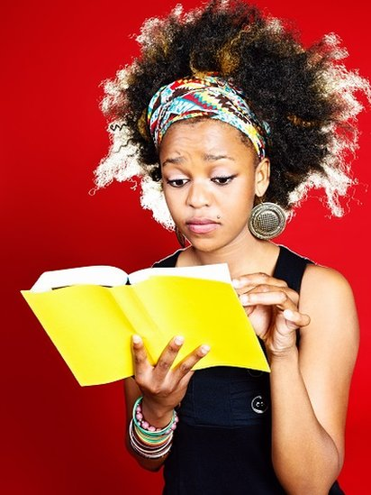 A worried-looking young woman reading a yellow-covered book.