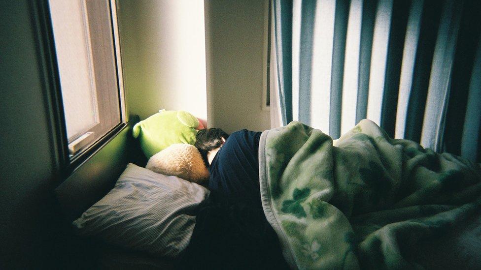 Una persona en la cama, cubierto de mantas y con la cabeza escondida