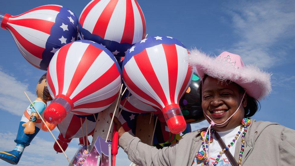 Una mujer sostiene globos con la bandera de Estados Unidos.