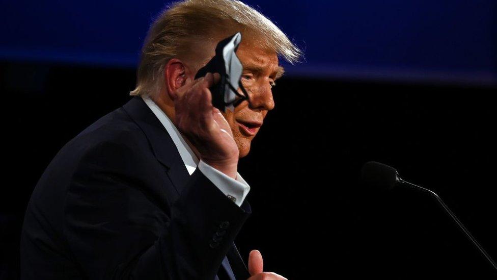 Donald Trump sosteniendo una mascarilla.