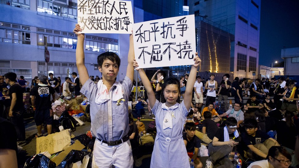 High-school demonstrators hold signs during a protest outside the headquarters of Legislative Council in Hong Kong on September 29, 2014