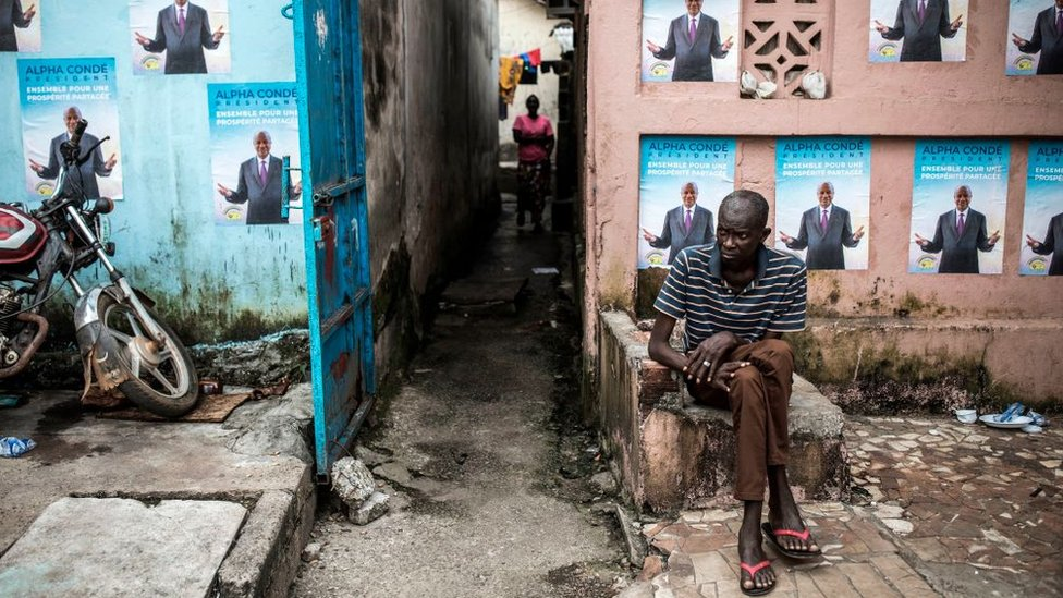 A man sits in front of campaign posters of President Alpha Conde in Conakry, on October 13, 2020.