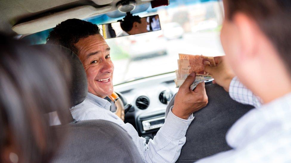 Taxista recibe dinero de un pasajero.