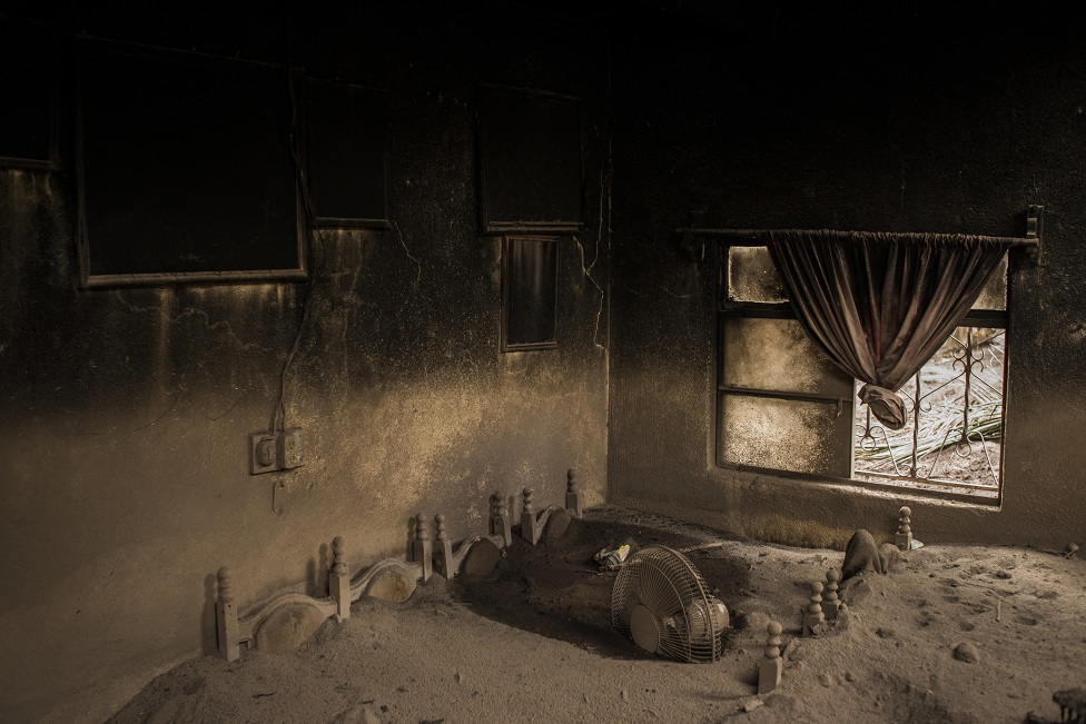 A damaged room in a house covered in ash