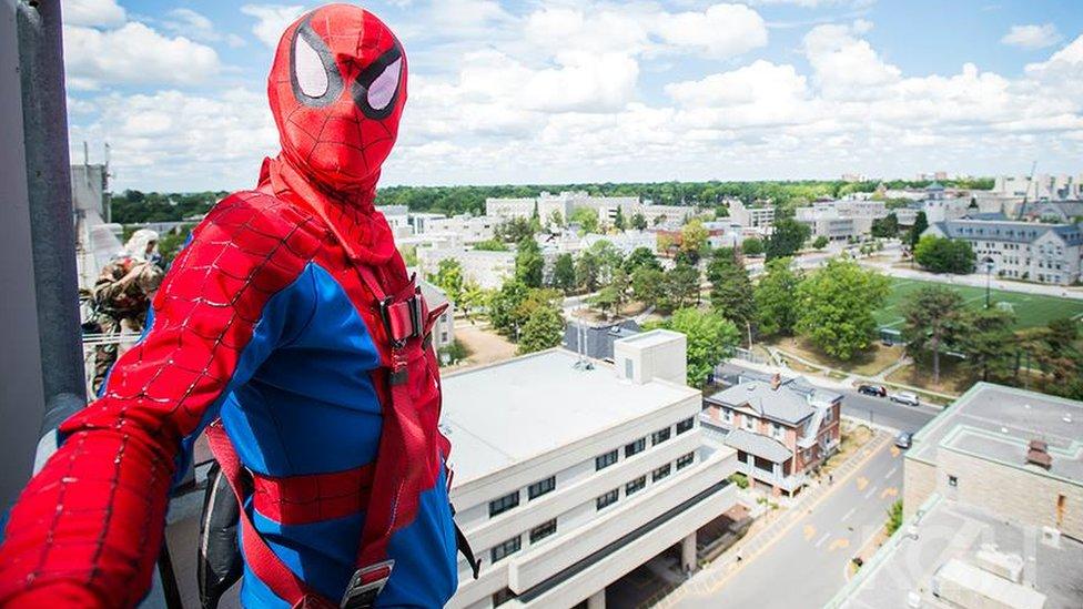Spiderman poses on the roof with the city stretching behind him