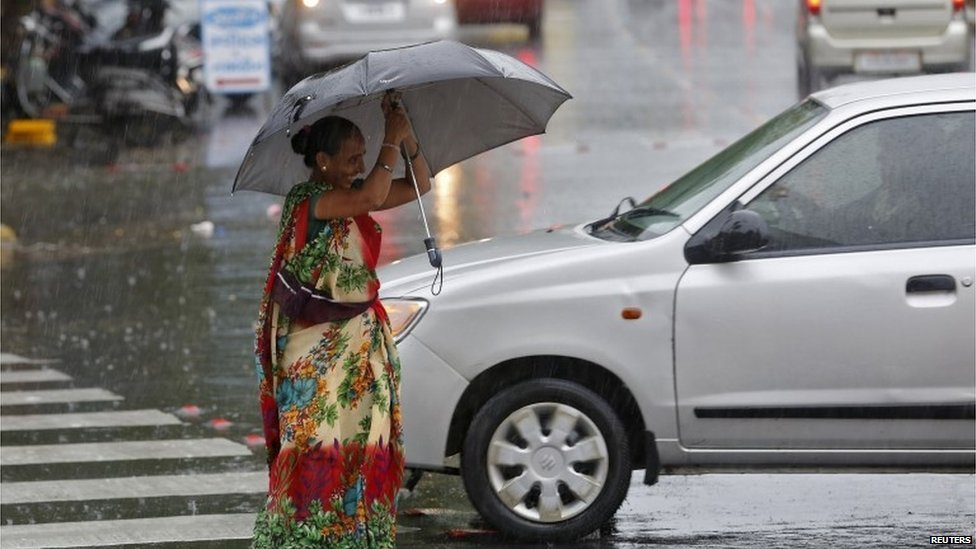 A woman tries to hold an umbrella as she walks through a busy road during a rain shower in Ahmedabad, India, June 24, 2015.