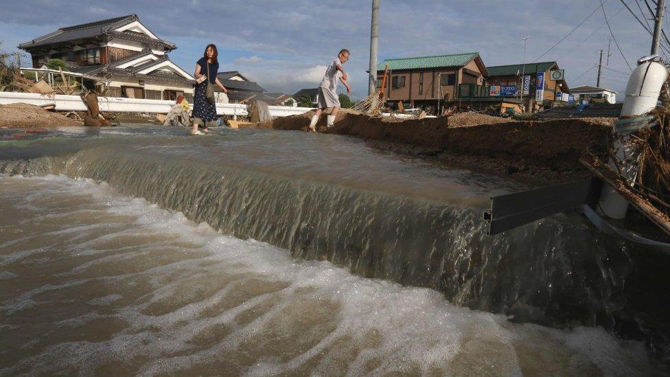 Residents cross an area still flooded in Kurashiki, Okayama prefecture on July 9, 2018