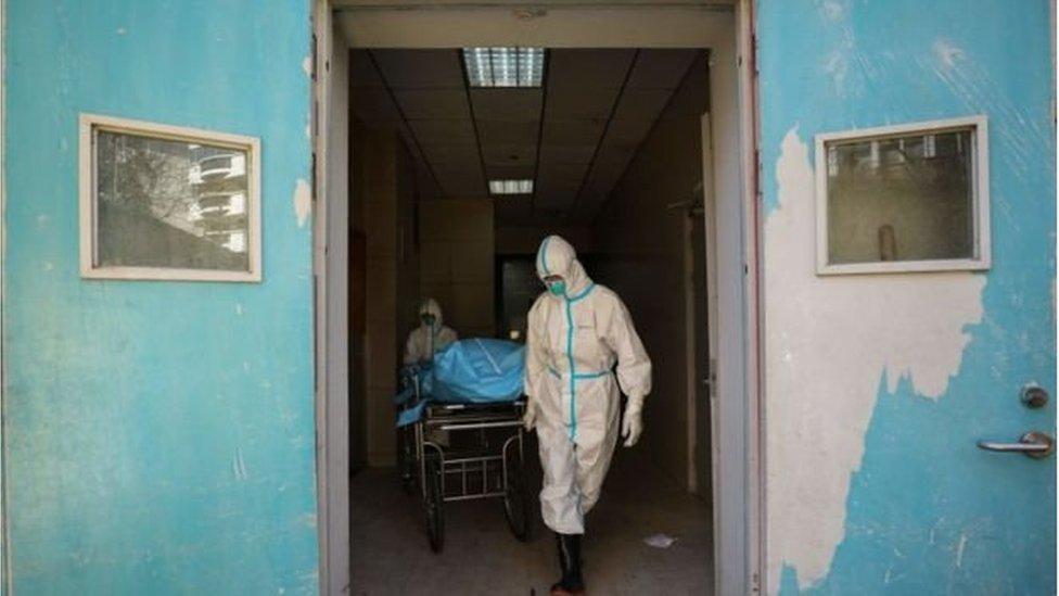 Petugas medis mendorong pasien virus corona yang telah meninggal dunia