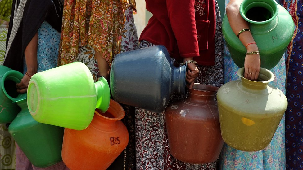 Indian residents in a district facing a drinking water shortage wait with plastic pots at a community tube well to collect drinking water in Bangalore on October 8, 2012.