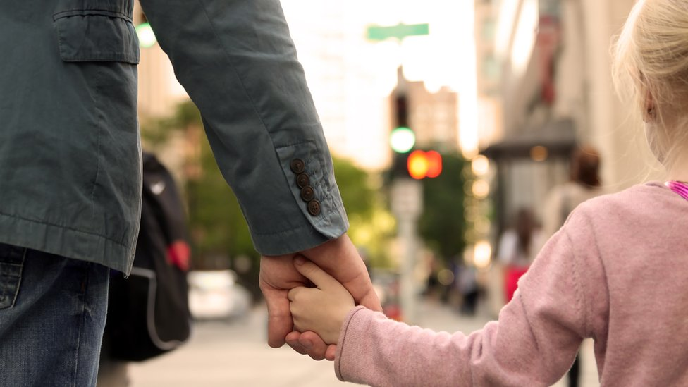 A close up of a father holding his daughter's hand as they walk along the street
