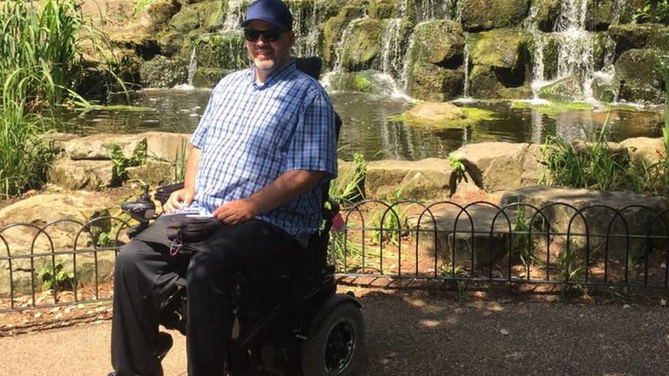 Dan sitting in his powerchair in front of a waterfall