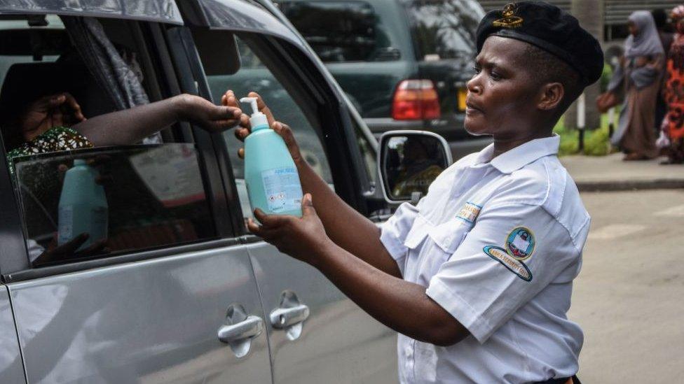 Un oficial de seguridad dispensa agua clorada a un pasajero en el Hospital Nacional Muhimbili en Dar es Salaam.
