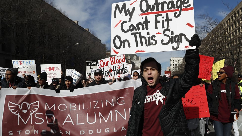 """Michael J. Weissman, 18, a student at Marjory Stoneman Douglas, where a mass shooting occurred last February 14 that left 17 dead, carries a sign as he and other participants hold the """"March for Our Lives"""" event"""