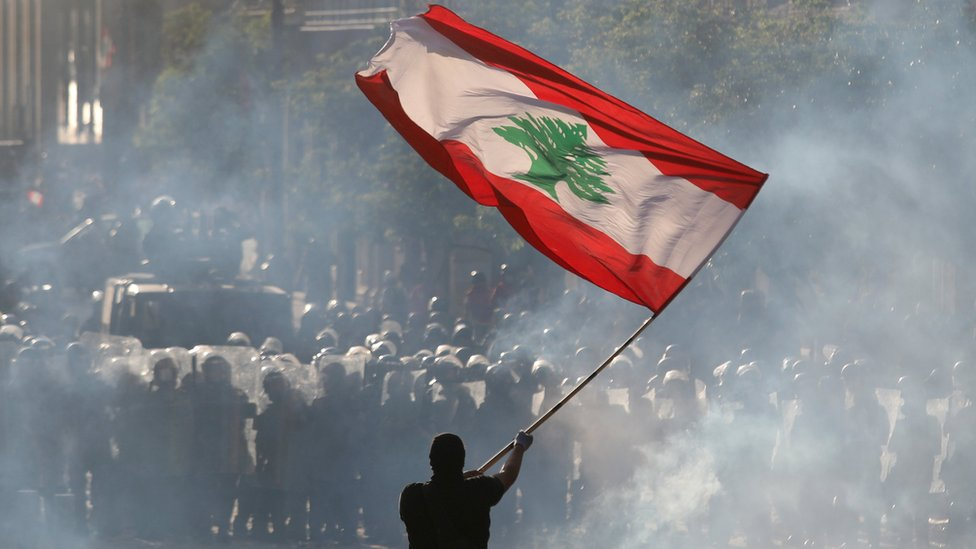 متظاهر يلوح بعلم لبنان في مواجهة قوات الشرطة