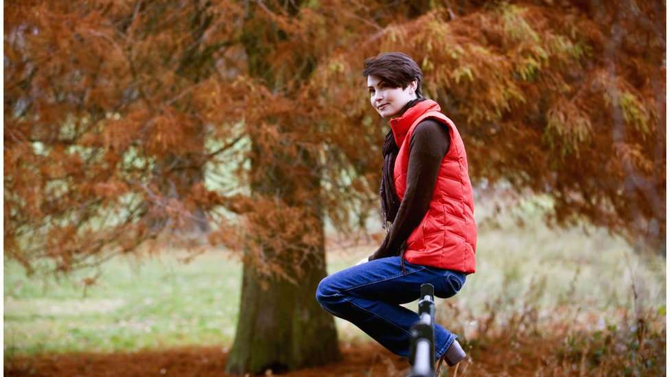 Woman sitting outdoors wearing a polo neck and gillet jacket