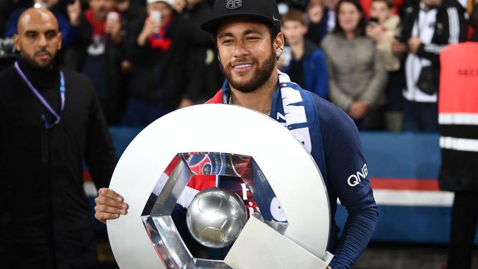 Neymar sosteniendo el trofeo de campeón