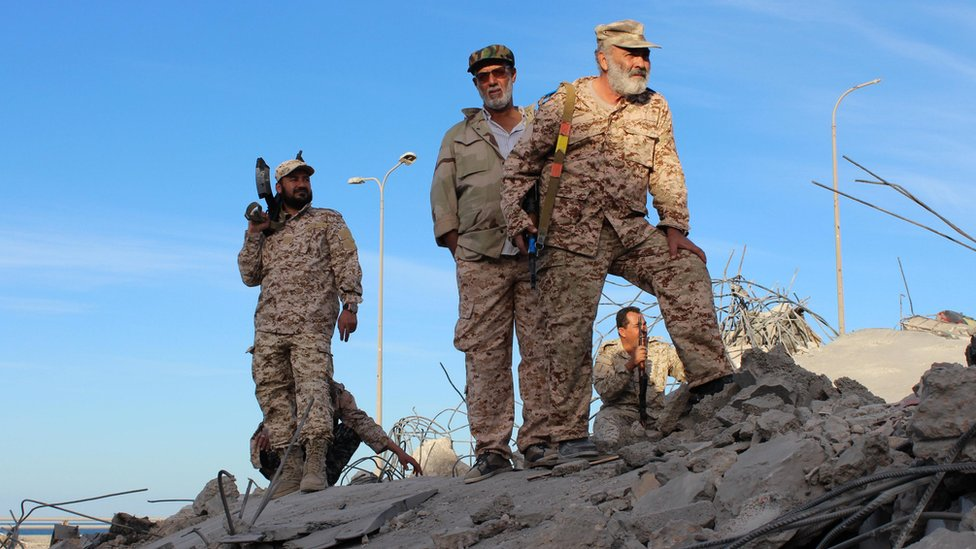 Fighters of Libyan forces allied with the U.N.-backed government stand atop the ruins of a house as they are close to securing last Islamic State holdouts in Sirte