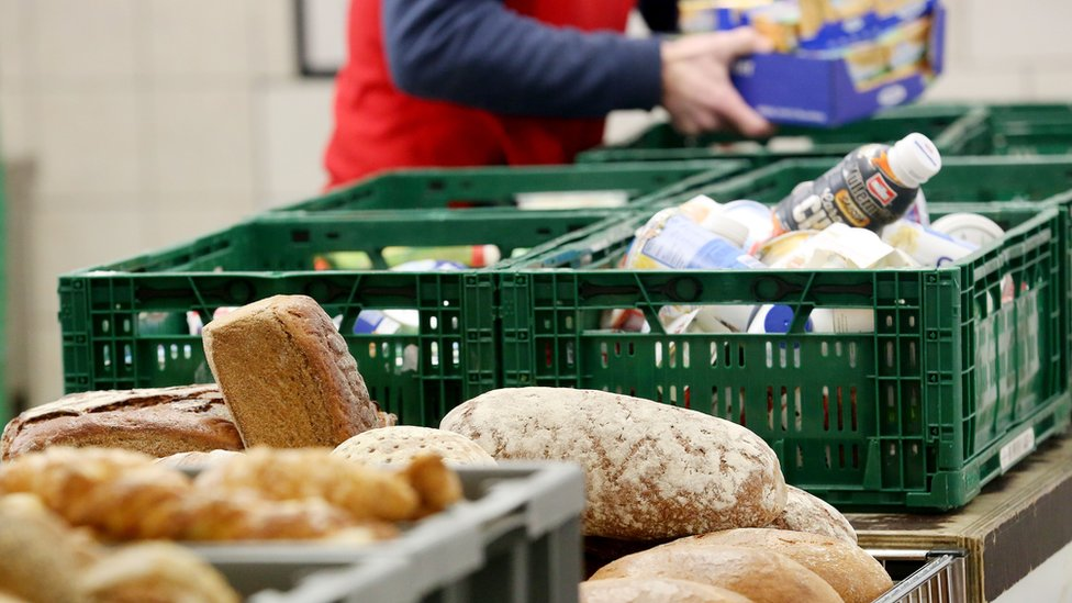 """A helper sorts food at the distribution site of the """"Essener Tafel"""" food bank distributing food to people in need in Essen, western Germany, on February 23, 2018"""