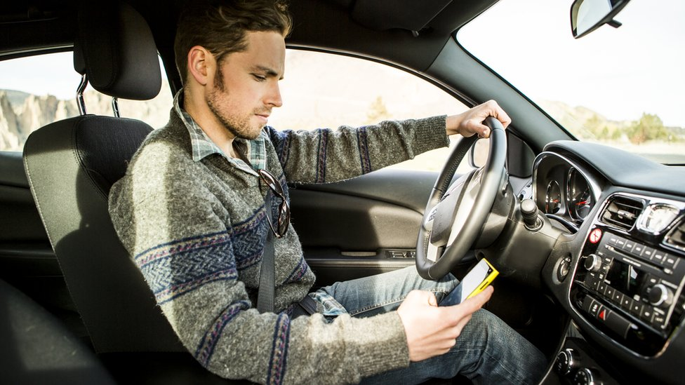 A man looking at his phone while driving