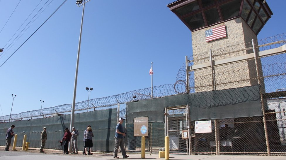 People walk past a guard tower outside the fencing of Camp 5 at the US Military's Prison in Guantanamo Bay, Cuba on January 26, 2017.
