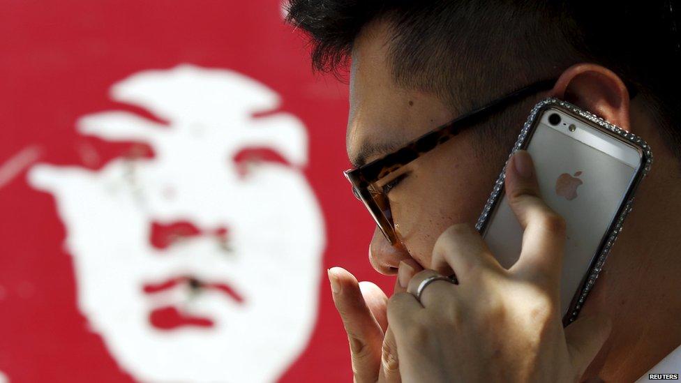 A man talks on an iPhone in Beijing, 24 July 2013