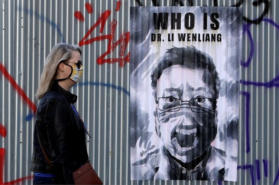 A woman wearing a face mask walks past a poster of late Li Wenliang in Prague