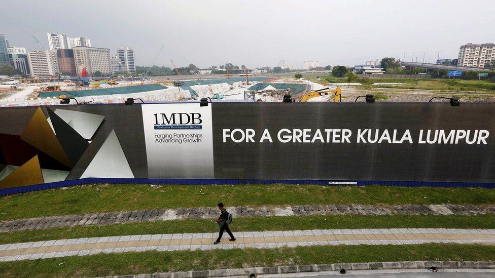 A man walks past a 1MDB billboard at the fund's flagship Tun Razak Exchange development in Kuala Lumpur, 1 March 2015.