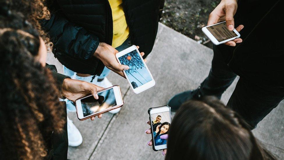 Cuatro jóvenes con sus teléfonos