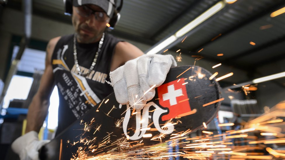 Man sharpens edges on skis at a Swiss factory