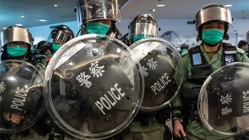 Riot police wearing protective masks stand guard during a demonstration in a shopping mall on 10 May in Hong Kong.