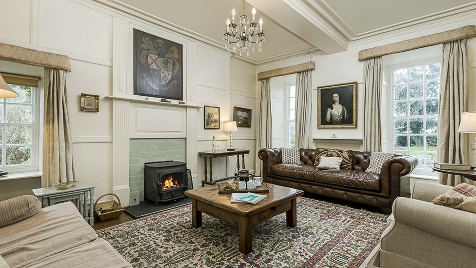 Inside a sumptuous lounge in the manor house, displaying family coat of arms on the wall