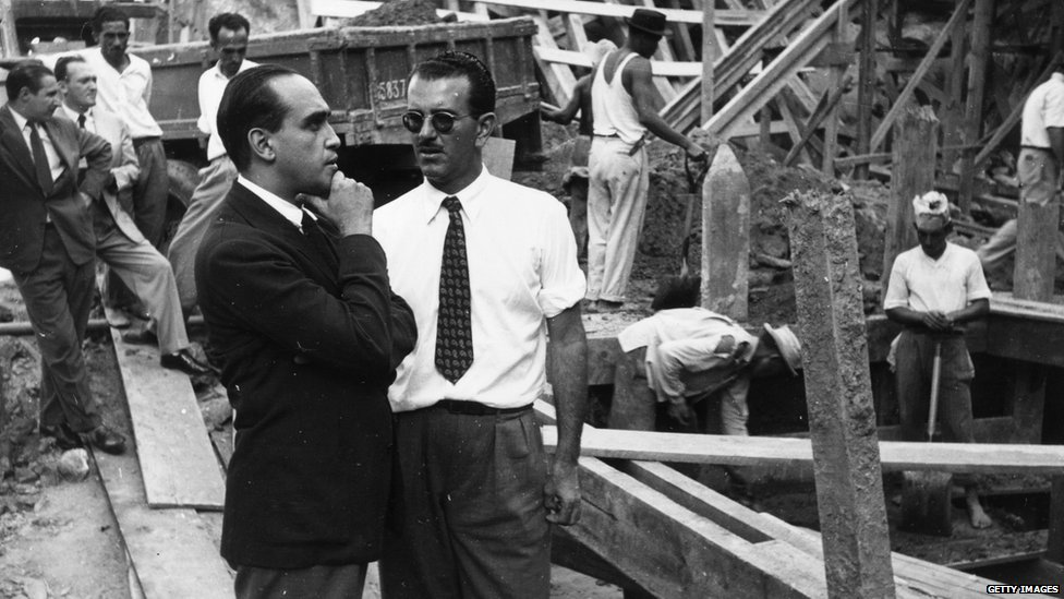 Hand on chin, Brazilian architect Oscar Niemeyer on the site of an office block in Rio de Janeiro for the weekly illustrated paper O Cruzeiro