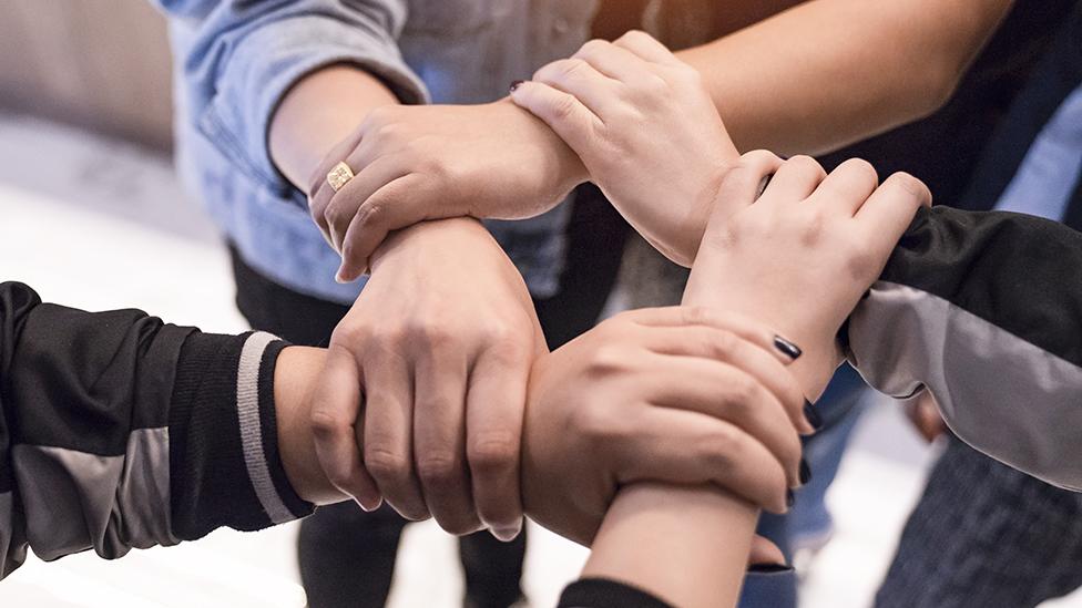 Cinco brazos entrelazados