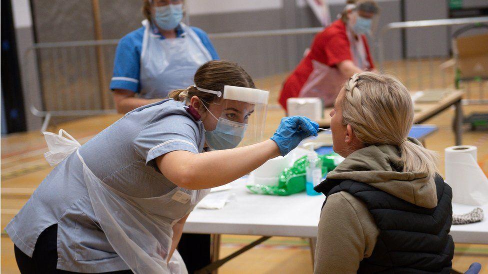 ممرضة تقوم باختبار التدفق الإيجابي لفيروس كورونا