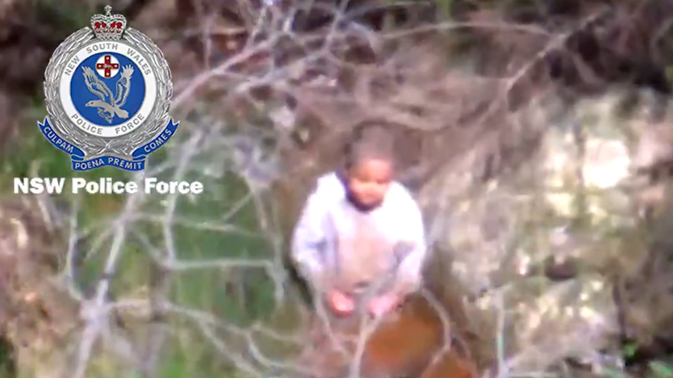 Aerial shot from police helicopter of AJ kneeling in a riverbed
