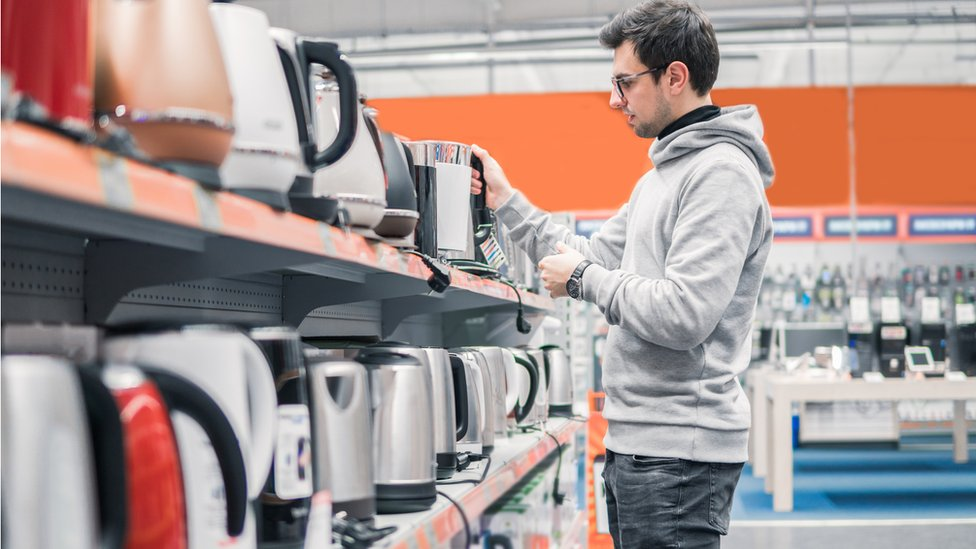 Customer choosing a kettle in a shop