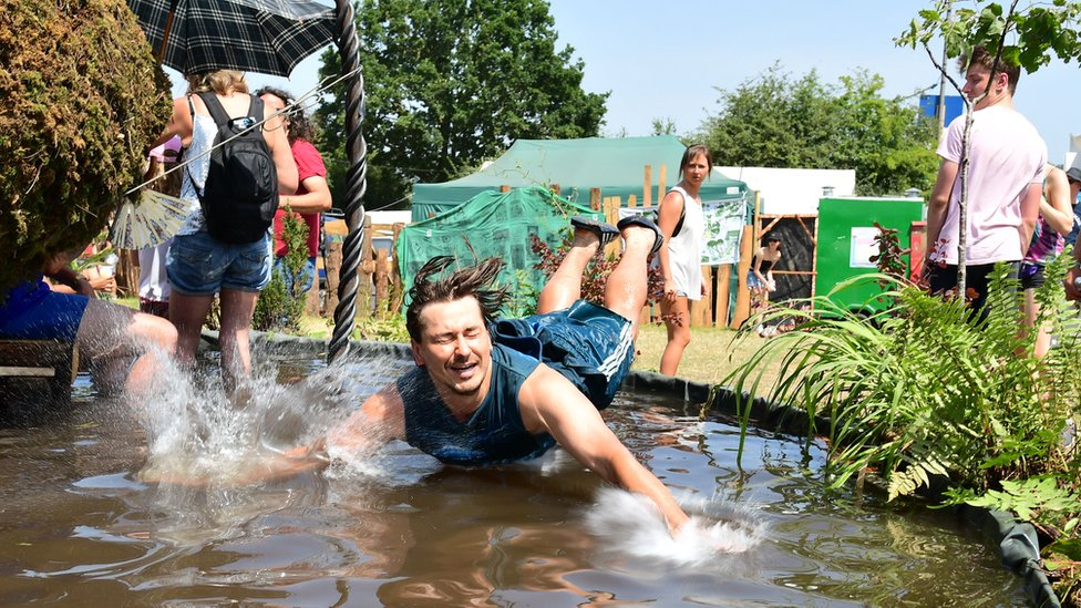A festival-goer jumps into a water feature to cool down on the Saturday of Glastonbury Festival at Worthy Farm