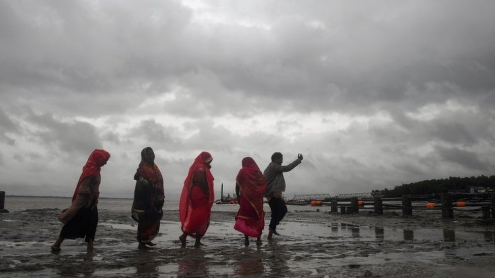 Hindu pilgrims walk back from the dock after a ferry service to Sagar Island was suspended due to the approaching Cyclone Bulbul in Kakdwip in West Bengal state