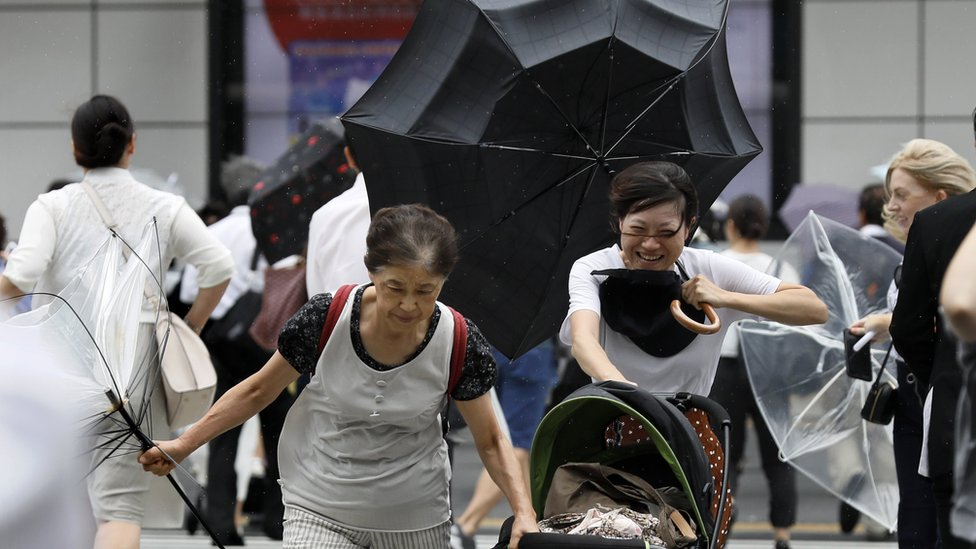 People with umbrellas walking through the storm