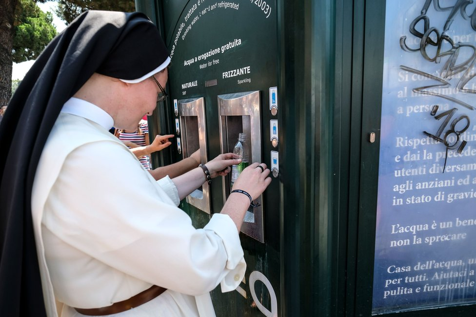 A nun takes water from a kiosk designed in the style of the hexagonal newspaper stands in front of the Ancient Colosseum, in central Rome
