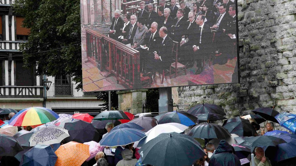 Mourners watch the funeral service outside the cathedral