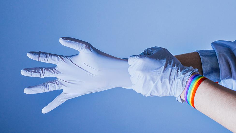 Personal de salud con guantes de latex y una cinta con los colores LGBT