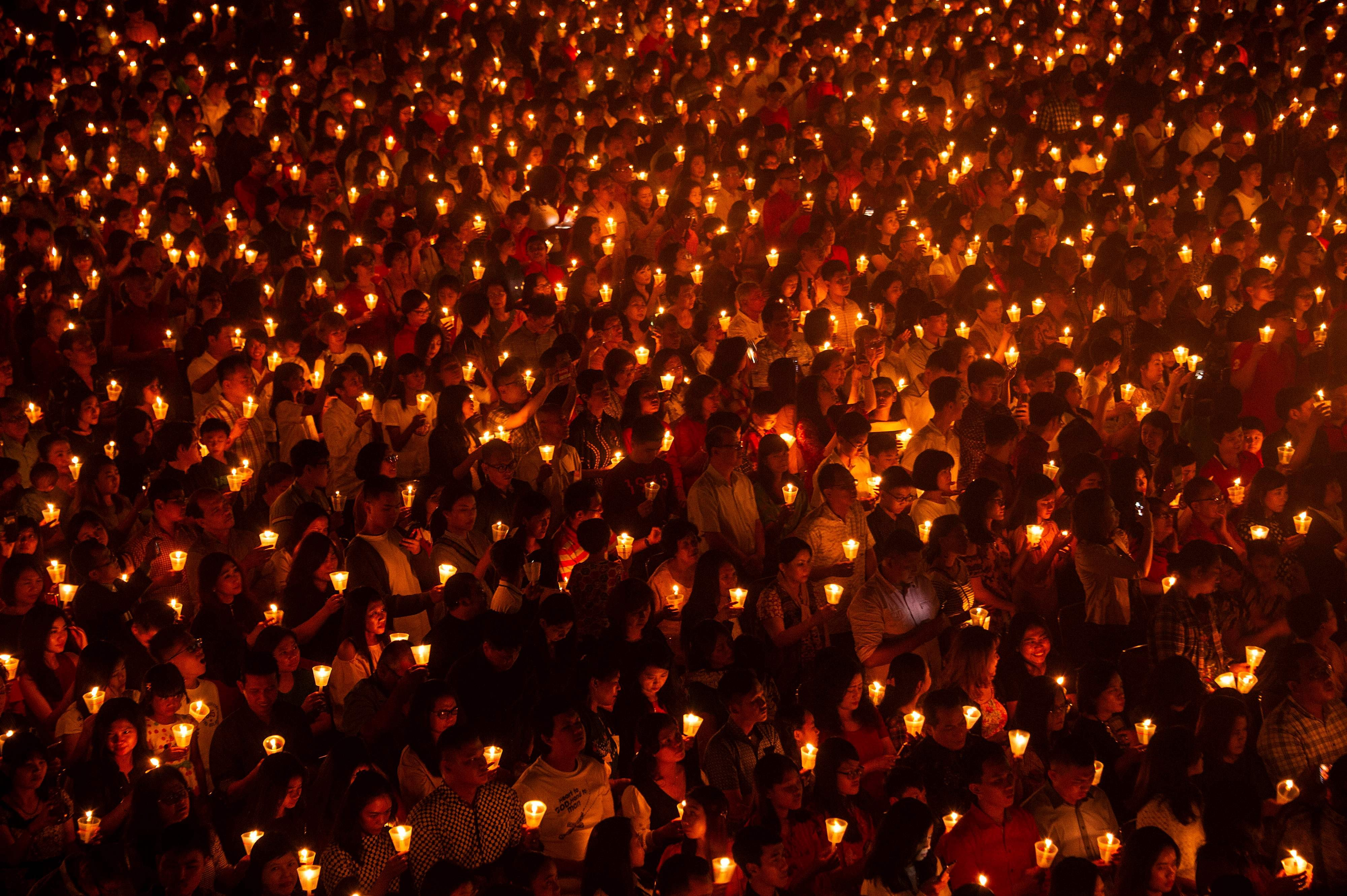 """Indonesian Christians attending mass on Christmas Eve at a stadium in Surabaya, the country""""s second largest city"""