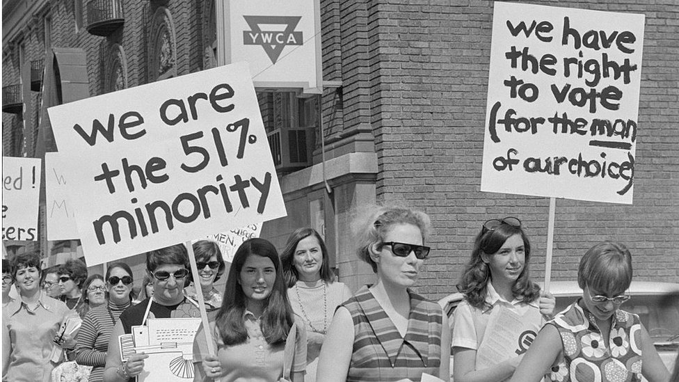 Pro-ERA marchers holding signs saying 'We are the 51% minority' and 'We have the right to vote (for the man of our choice)'