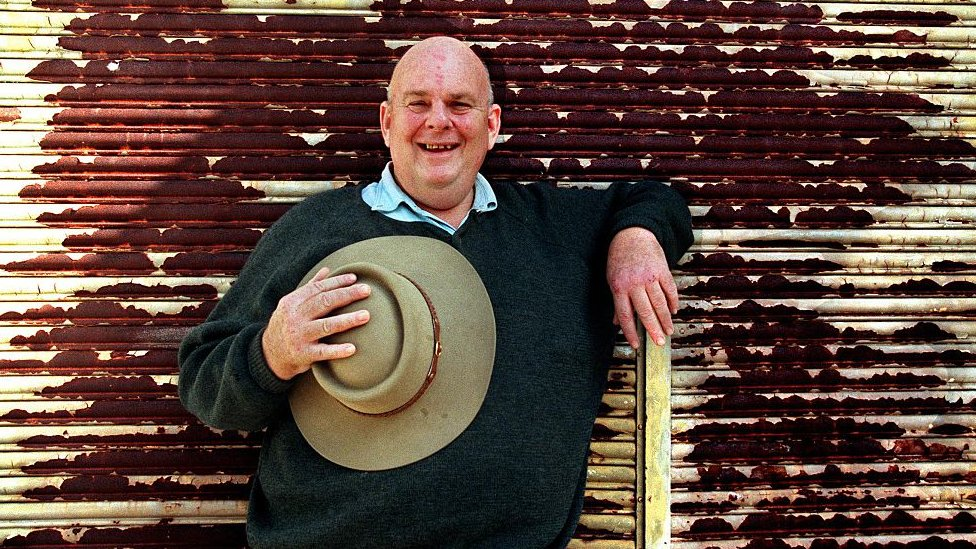 Les Murray stands holding an Akubra hat against a rusted wall