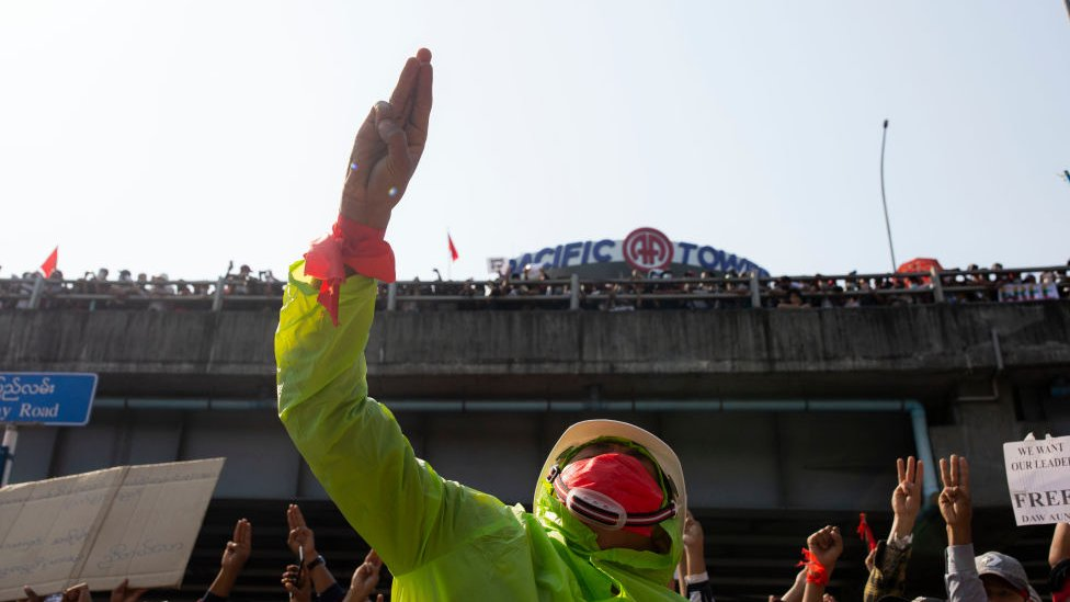 Seorang pengunjuk rasa yang mengenakan topeng memberi hormat dengan tiga jari