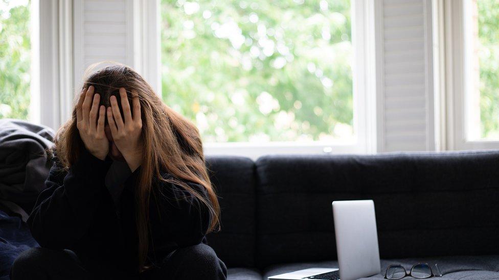 Una mujer apoyando la cabeza en las manos al lado de una computadora.