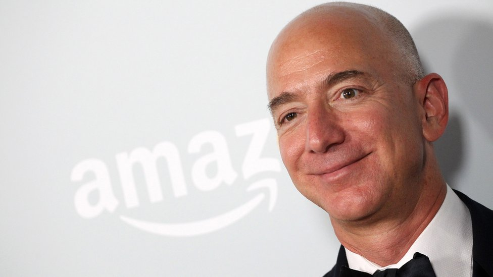 Jeff Bezos standing in front of an Amazon sign