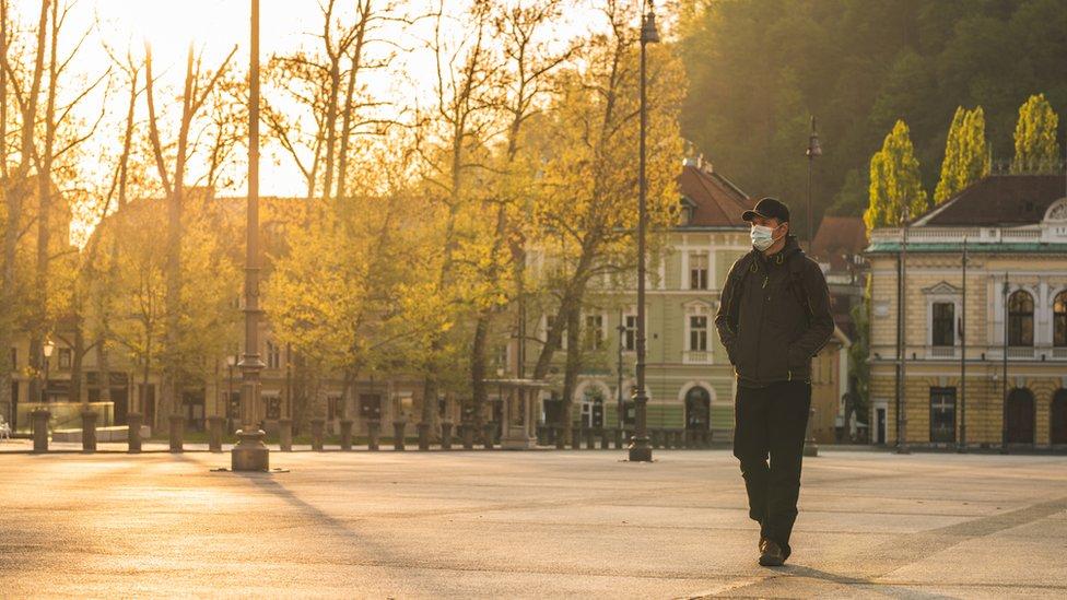 Hombre con mascarilla caminando por ciudad desocupada